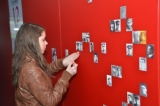 Ilina Theeten adds portraits on the photo wall at Lijssenthoek